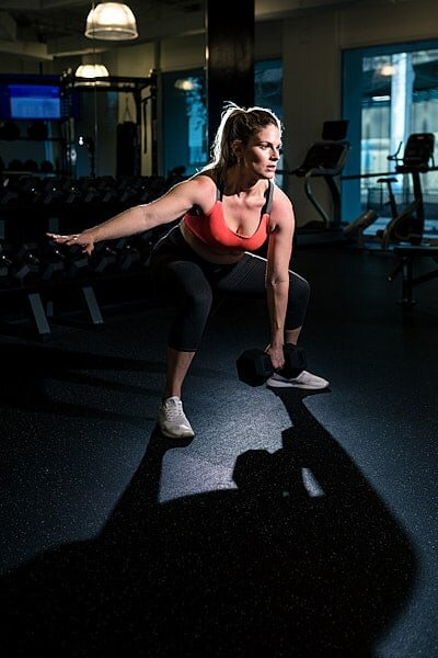 dramatic portrait of mom lifting weights in Atlanta gym