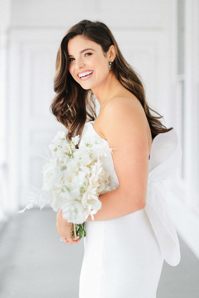 Bride laughing holding a white bouquet