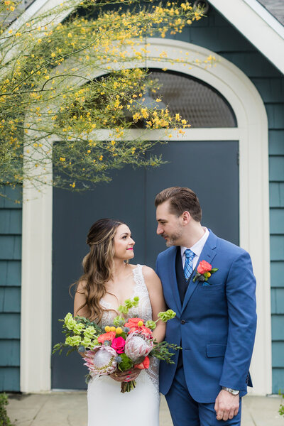 Bride and groom look at each other warmly while holding bouquet on outdoor staircase on their wedding day