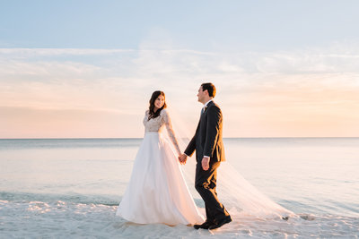 bride & groom walking on beach