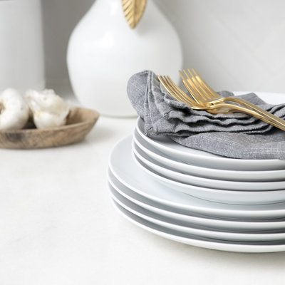 White plates, grey linen napkins, and gold silverware stacked on countertop