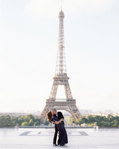 Husband dips wife while dancing in front of Eiffel Tower