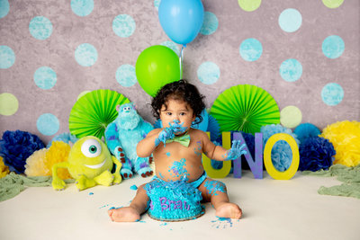 first birthday cake smash against a blue and green polka dot background