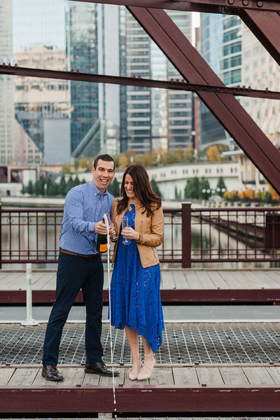 Couple pop open champagne on Kinzie Street Bridge in Chicago.