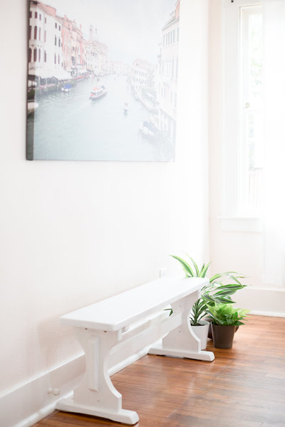 Lyndi and Jason's dining room white bench with green houseplants next to it and large canvas of Venice Grand Canal on wall