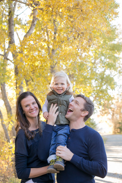 Husband, wife and daughter posing during a photoshoot in a local Denver park.