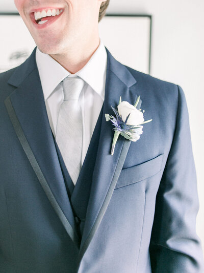 groom wearing blue suit and boutonniere