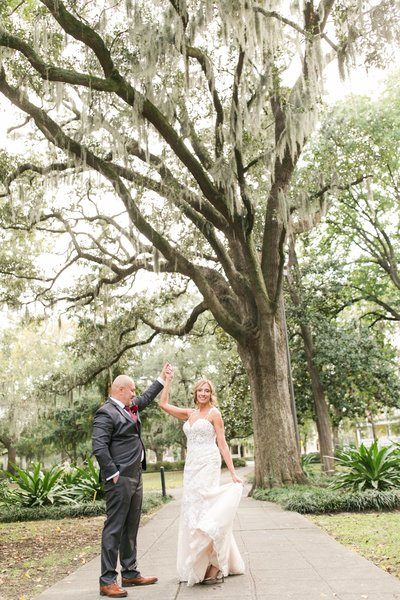 groom twirling bride in forsyth park after their elopement at the gastonian ins avannah