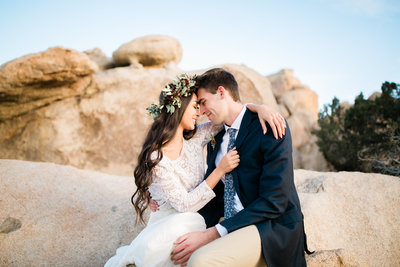 having just eloped, a couple sitting on joshua tree boulders snuggle in close and smile.