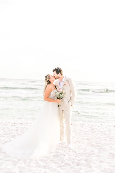 Bride and groom kiss on Charleston beach on their wedding day