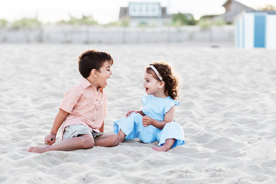 Brother and sister sitting on the beach playing