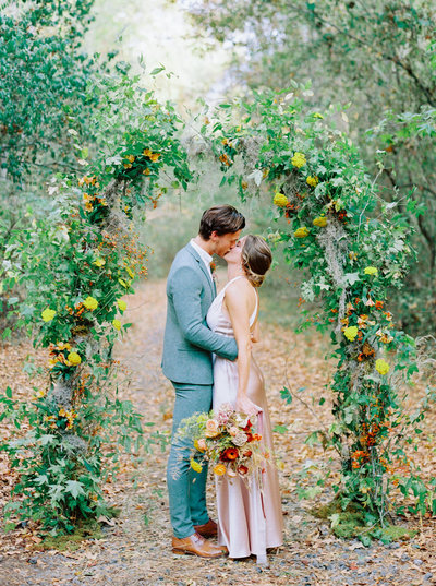 Microwedding underneath a flower arch, with groom kissing bride