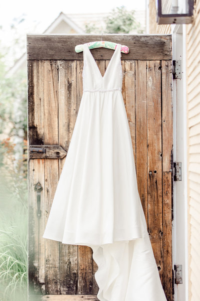 Wedding dress hanging from a wooden door at the Inn at the Round Barn.