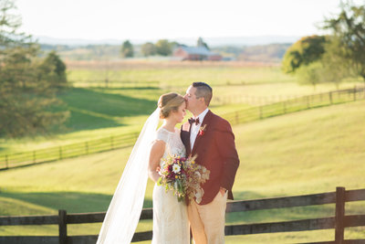bride and groom hugging in rolling hills at hermitage hill farm wedding in waynesboro by virginia wedding photographer