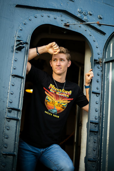 Teen boy boys in train door during senior photography session