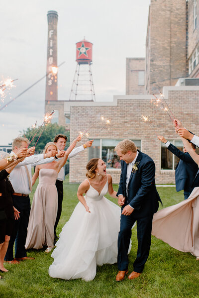 Bride & Groom looking at each other and laughing during their sparkler send off
