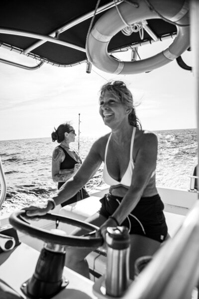 Black and white image of a blonde woman driving a fiching boat and a brunette women holding a fishing pole