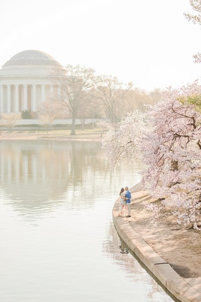 couple kissing by the tidal basin during the cherry blossoms in washington dc by costola photography
