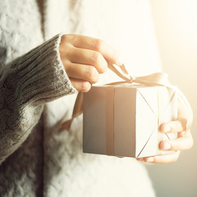 A woman opens a gift card from Karissa Van Tassel Photography