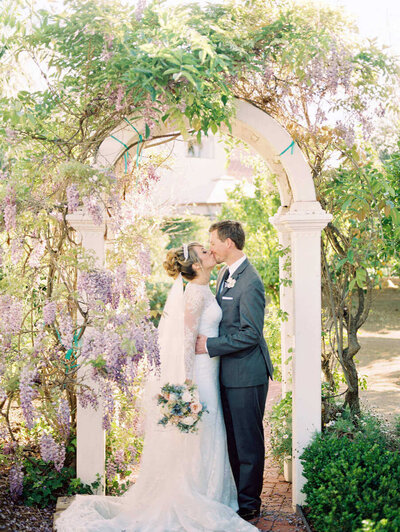 Lilac covered arch with bride in catheral veil and groom kissing in SoCal
