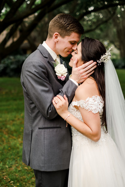 Groom lovingly caressing bride's face and bride hold his arm while intimately touching noses on their wedding day