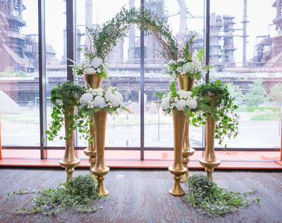 White and green floral with gold accents vases ceremony backdrop