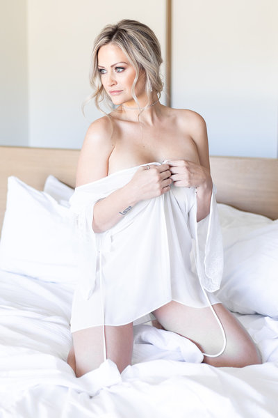 Heather Godby staring at the window from bed, wearing a white lingerie piece at civana carefree during her boudoir session