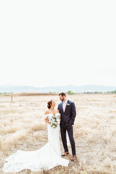 bride and groom in wedding attire  standing in colorado field