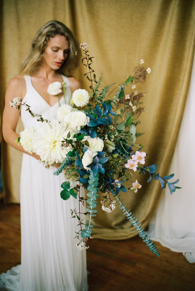 Blue and white whimsical floral bouquet in front of gold drapery held by a bride in soft cream tulle.
