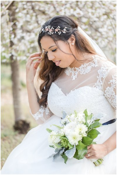 Bride in front of white blossoms at the Golden Horseshoe Inn wedding venue