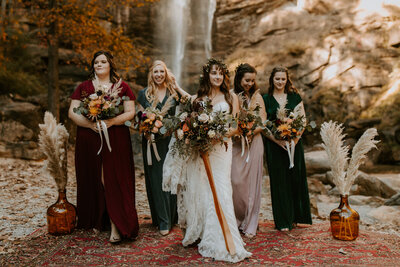 bride standing with bridesmaids with waterfall in background