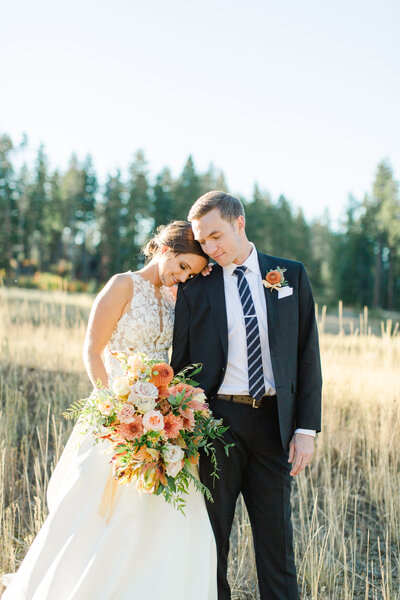 bride holding bouquet and resting her head on groom's shoulders as he looks down at the ground