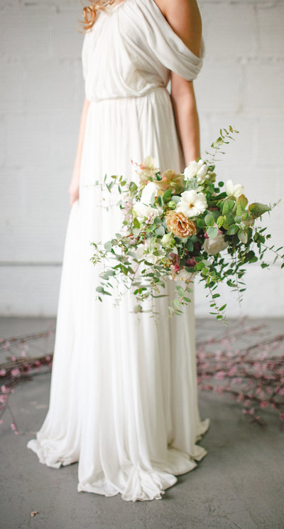 grecian wedding dress in concrete loft with beautiful floral bouquet