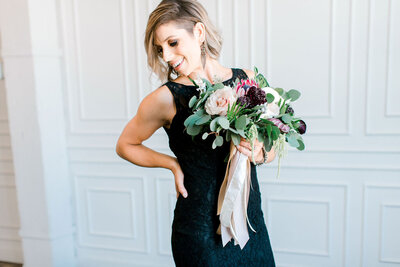 woman holding bouquet of flowers standing looking down in black dress