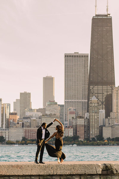 Couple twirl in front of the Chicago skyline for engagement photo.