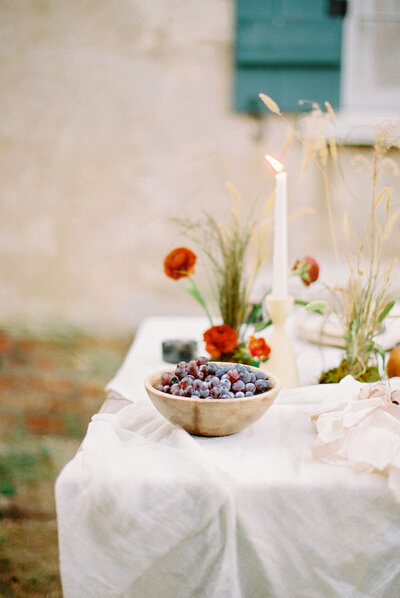 Hand-carved wooden bowl of fresh grapes as table decor for a cozy autumn elopement