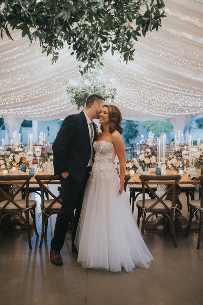 Elyse Jennings Weddings bride and groom at tented reception with twinkle lights