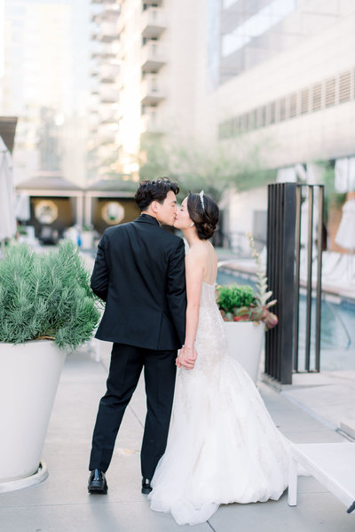 bride and groom walking away giving eachother a kiss on the rooftop of the w hotel in austin by the pool by atlanta wedding photographer lane albers photography