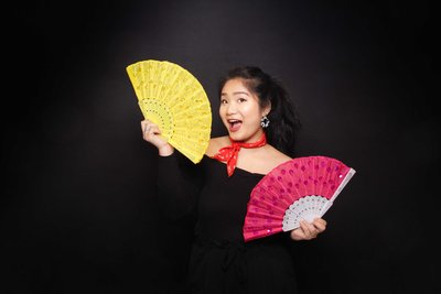 girl smiling while holding fans as props on a black backdrop