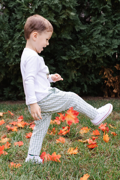A little boy kicks fall leaves around