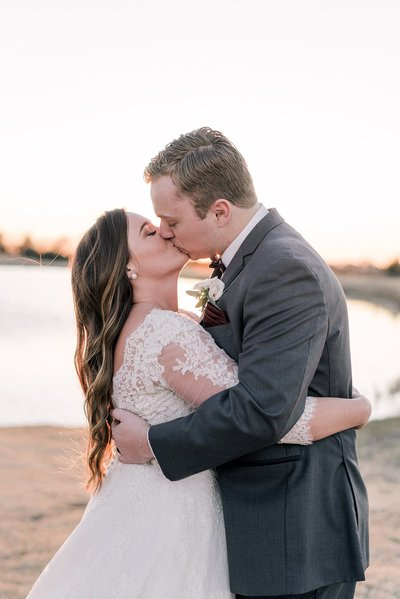 bride and groom kissing during sunset portraits at dallas wedding venue the grand ivory by catie ann photography