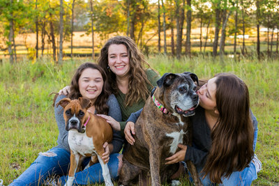 Corry's 3 teenage daughters and 2 dogs smile in field for photo