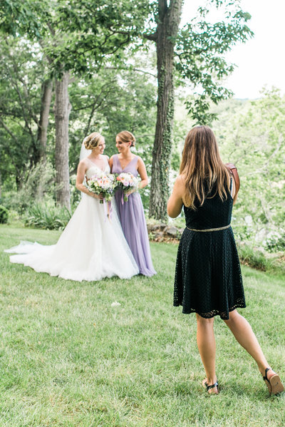 Image of a photographer photographing a bride and her maid of honor.