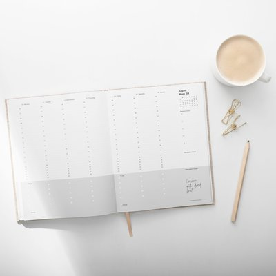 planner sitting on table with coffee and pencil