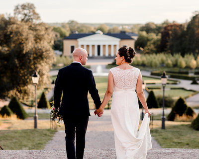 Weddingcouple walking towards tge bothancal garden in Uppsala hand in hand looking at each other in golden hour