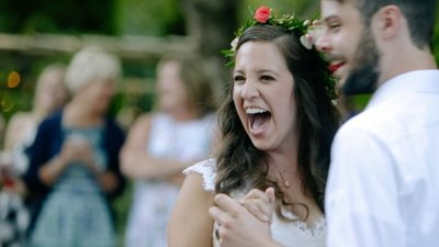 bride in flower crown laughing during first dance