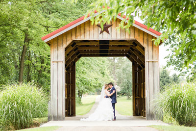 Bride and Groom under Covered Bridge at Brookside Farm photographed by Photographer Akron Ohio Loren Jackson Photography