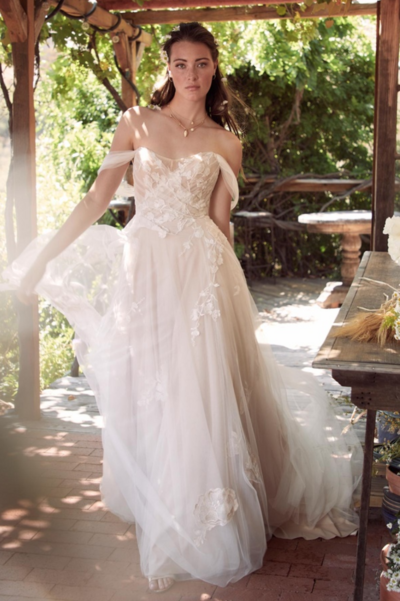 Maudie is enveloped in custom botanical embroidery. This boho beauty features an off the shoulder neckline, romantically draped sleeves, and a soft net, tie back for an extra-whimsical finish.