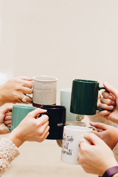 "Seven hands holding seven ceramic mugs together in a ""cheers"""