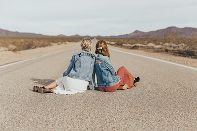 two women sitting in road wearing denim jackets